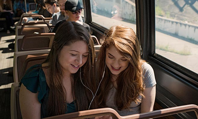 Two girls listening to music on a bus