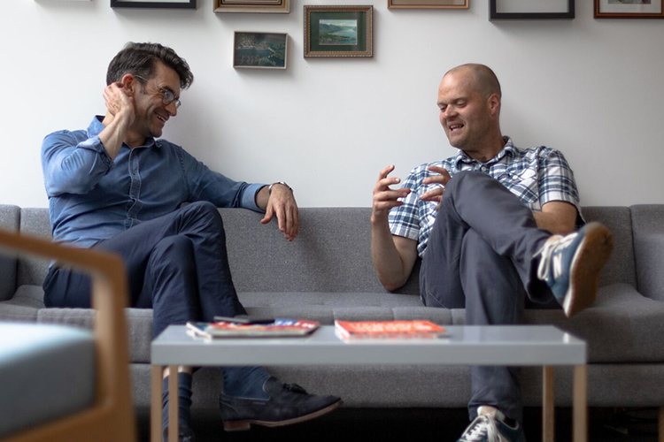 cxpartners' co-founders, Richard and Giles, sharing a laugh while sitting on a sofa in the cxpartners office.